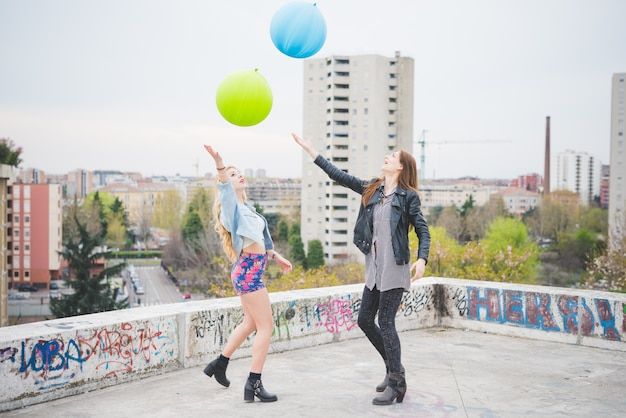 Two beautiful blonde and brunette girls playing with baloons