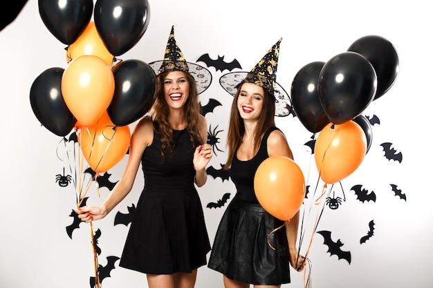 검은 드레스와 모자를 쓴 두 명의 아름다운 갈색 머리 소녀가 검은색과 주황색 풍선을 들고 있습니다. 할로윈 .