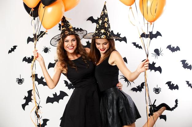 검은 드레스와 마녀 모자를 쓴 두 명의 아름다운 갈색 머리 소녀가 검은색과 주황색 풍선을 들고 있습니다. 할로윈 . 프리미엄 사진