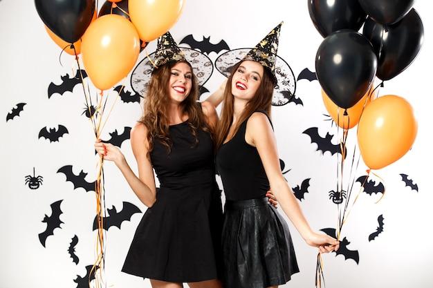 검은 드레스와 마녀 모자를 쓴 두 명의 아름다운 갈색 머리 소녀가 검은색과 주황색 풍선을 들고 있습니다. 할로윈 .