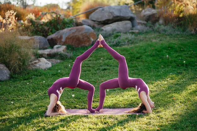 Two beautiful brunette woman wearing tight active wear performing yoga poses in a park on purple mats with soft sun flares coming through the trees