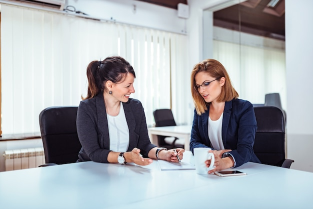 Two beautiful business woman talking at conference room.
