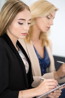 Две красивые бизнес-леди сидят на семинаре и что-то пишут. бизнес-образование и концепция успеха