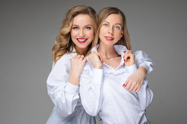 Две красивые кавказские девушки в белых рубашках, картина изолирована на серой стене
