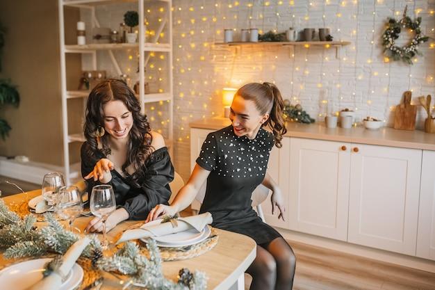 新年のキッチンの背景にあるクリスマスのダイニングテーブルで笑っている2人の美しい陽気な幸せな若い女の子の友人