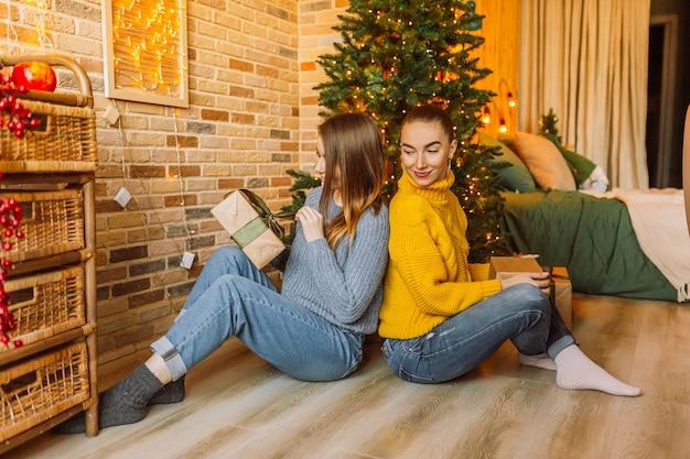 두 명의 아름답고 쾌활한 행복한 어린 여자친구가 집에 있는 새해 나무 배경에서 크리스마스 선물을 줍니다