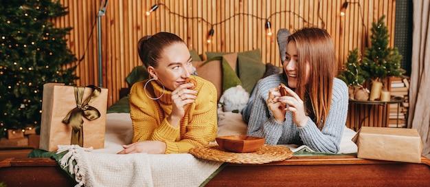 두 아름 다운 쾌활 한 행복 한 젊은 여자 여자 친구 집에서 새해 나무의 배경에 크리스마스 선물을 제공