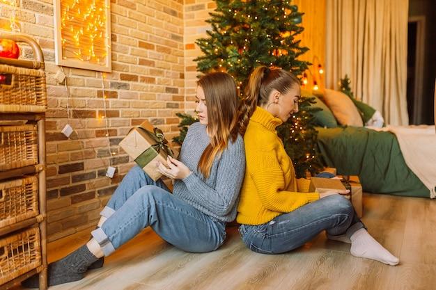 2人の美しい陽気な幸せな若い女の子のガールフレンドは、自宅で新年の木にクリスマスプレゼントを贈ります