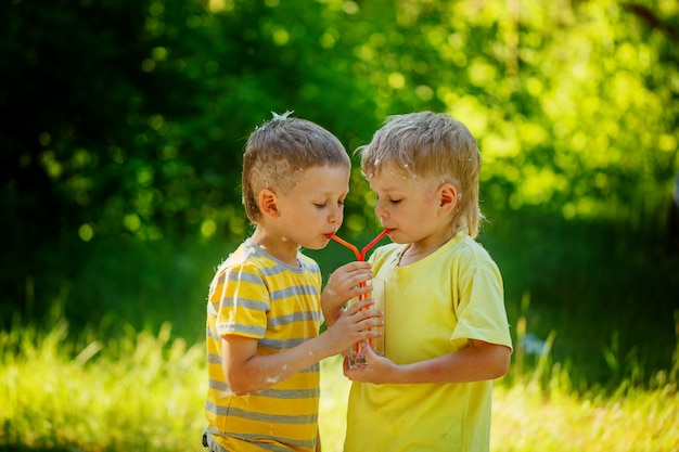 Two beautiful children, boy friends,  drinking water in the park