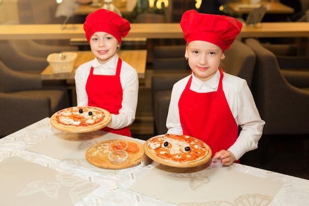 식당에서 흰 셔츠와 빨간 앞치마를 입은 두 명의 아름다운 요리사 소녀가 피자를 만듭니다.