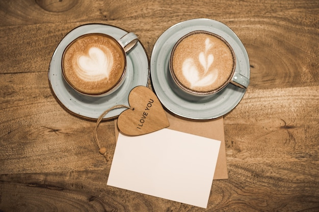 Two beautiful cups of coffee with a heart shape, craft envelope, white blank sheet of paper and wooden heart with the words i love you on a wooden background. valentine's day concept. selective focus.