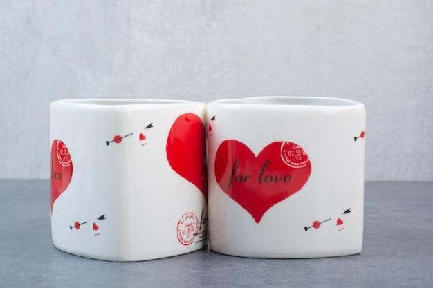 灰色の表面に2つの美しいカップ