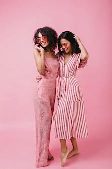 Due belle amiche dai capelli scuri con la pelle abbronzata in posa. foto a figura intera.