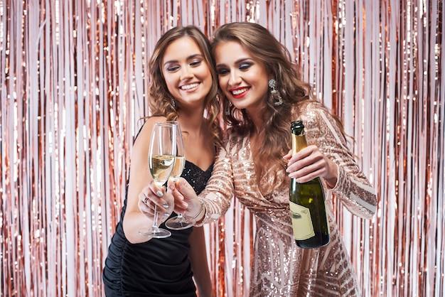 Two beautiful elegant women clinking champagne glasses.