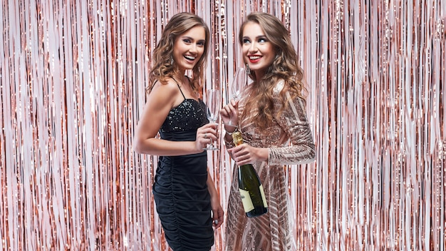 Two beautiful elegant women drinking champagne against sparkling decoration