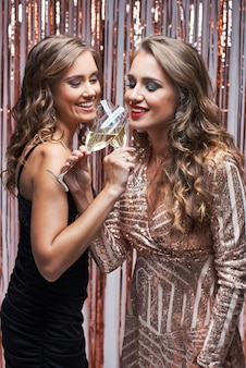 Two beautiful elegant women in evening dresses drinking champagne.
