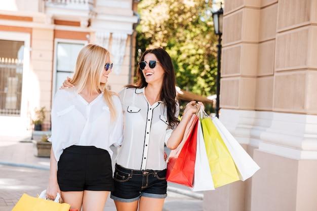 一緒に買い物袋を持って外でポーズをとる2つの美しいファッションモデル