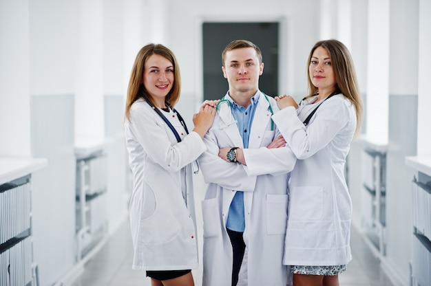Two beautiful female doctors and one male in white coats posing in the hospital with stethoscope.