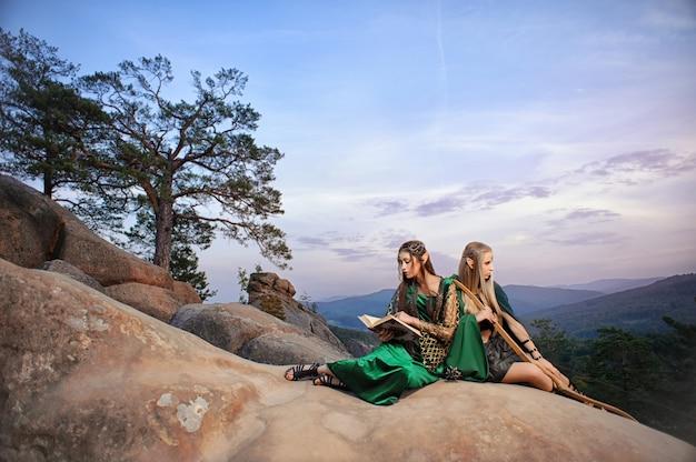 Две красивые женские эльфы, сидящие на вершине горы