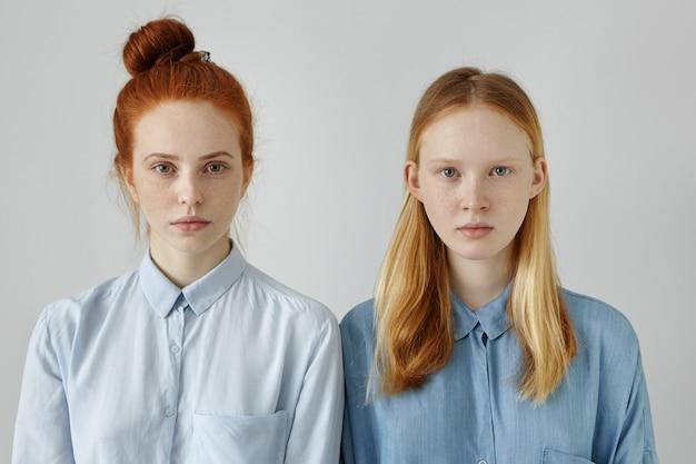 灰色の壁でポーズのシャツの2つの美しい女性。自信を持って表情を見ている金髪の妹の近くに髪のお団子が立っている赤髪の若い女性