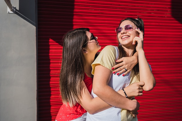 笑顔、抱擁、楽しんでサングラスをかけた2人の美しい友人