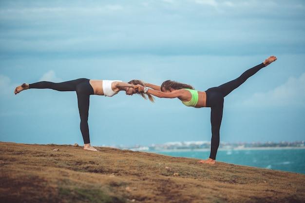 Two beautiful girl doing yoga