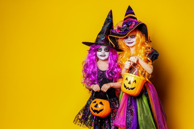 Two beautiful girl in a witch costume scaring and making faces