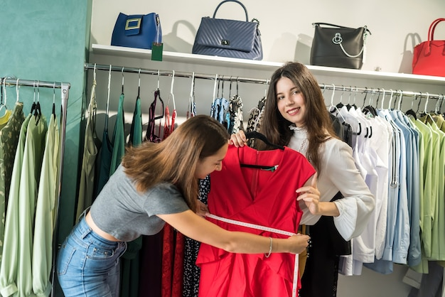 Two beautiful girlfriends choose a beautiful red dress for a ball in a stylish store