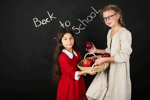 本と黒の背景にりんごのバスケットに座っている2つの美しいガールフレンド女子学生