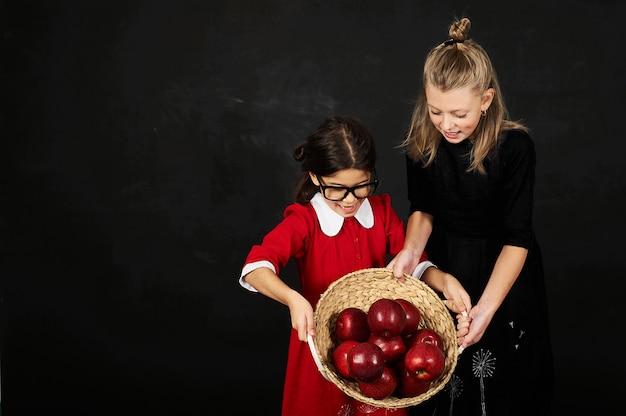 本と黒の背景にりんごのバスケットを持つ2つの美しいガールフレンド女子学生