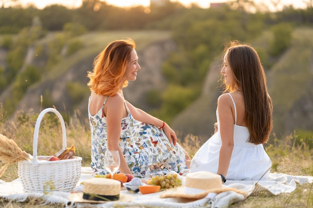 Two beautiful girlfriends spend time together on a picnic