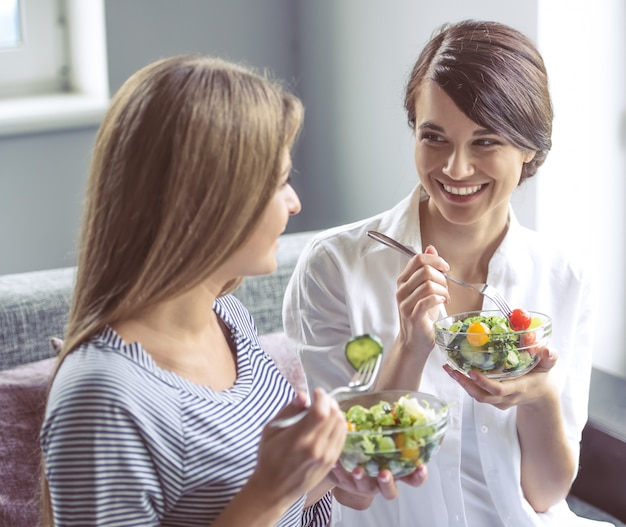 Two beautiful girls are eating salad.