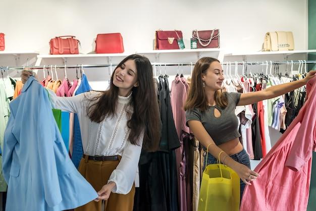 2人の美しい女の子がお祝いのためにファッションストアで新しい服を選びます。ライフスタイル