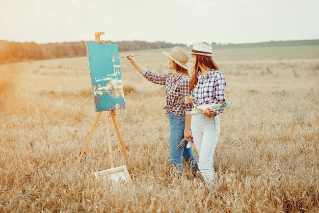 Two beautiful girls drawing in a field