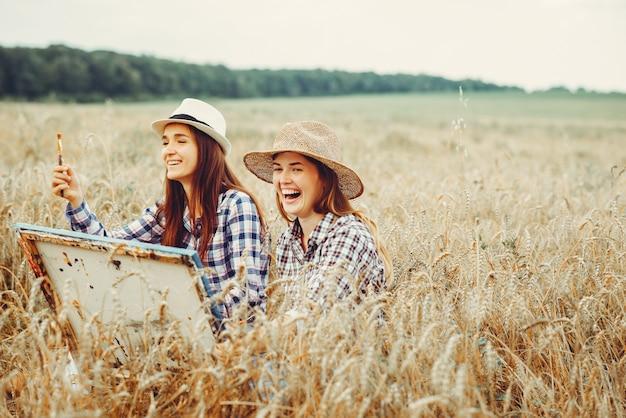 Two beautiful girls drawing in a field