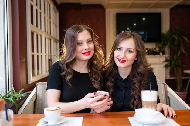 2人の美しい女の子がコーヒーを飲み、電話で見る