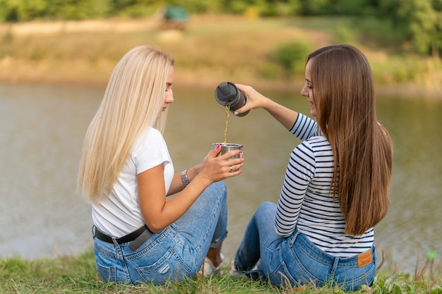 Two beautiful girls enjoy nature and drink hot tea on lakeshore with beautiful view