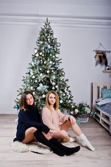 Two beautiful girls friends wear in warm sweater and leg warmers
