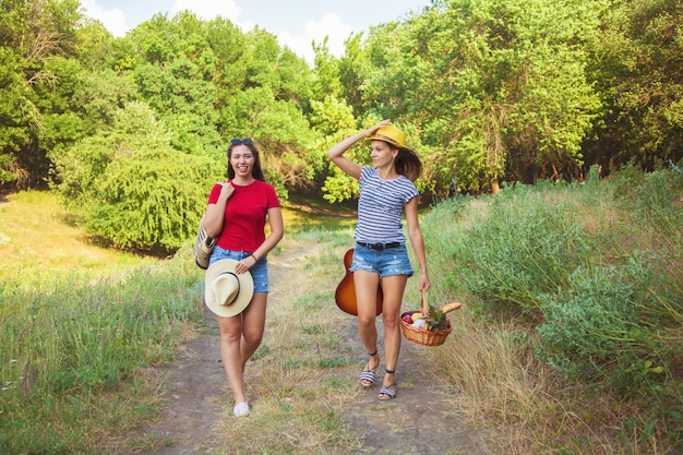 Two beautiful girls go on a picnic on the path in the forest