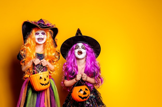 黄色の背景に魔女の衣装と帽子をかぶった2人の美しい女の子が怖がって顔を作っています。