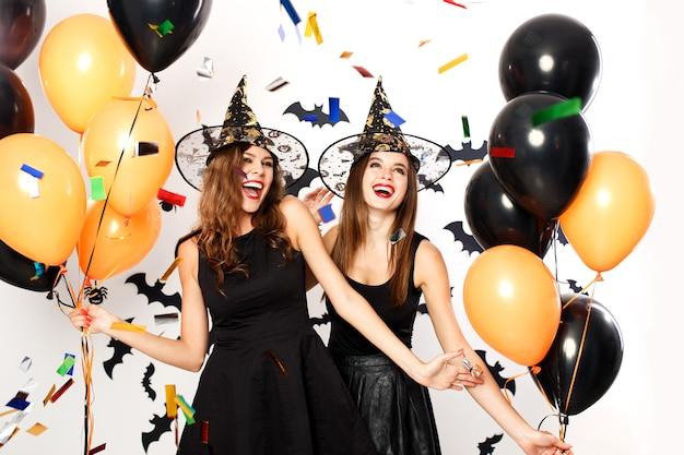 검은 드레스와 마녀 모자를 쓴 두 명의 아름다운 소녀가 검은색과 주황색 풍선과 색종이 조각으로 즐거운 시간을 보냅니다. 할로윈 파티 .