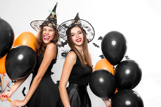 검은 드레스와 마녀 모자를 쓴 두 명의 아름다운 소녀가 검은색과 주황색 풍선으로 즐거운 시간을 보내고 있습니다. 할로윈 .