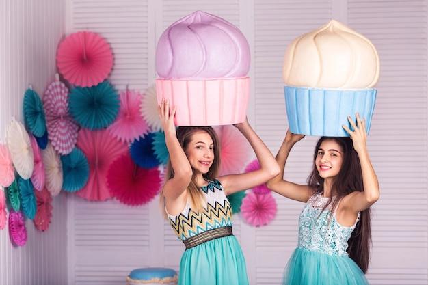 青いドレスを着た2人の美しい女の子がマカロンの装飾が施された巨大なケーキを手に持っています