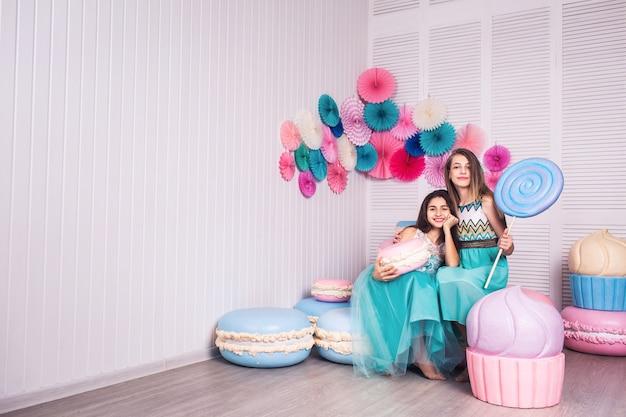 青いドレスを着た2人の美しい女の子が、マカロンの装飾が施されたスタジオで巨大なキャンディーとマカロンを手に持っています。