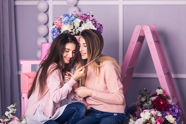 ジーンズとピンクのセーターの2人の美しい女の子が笑っています