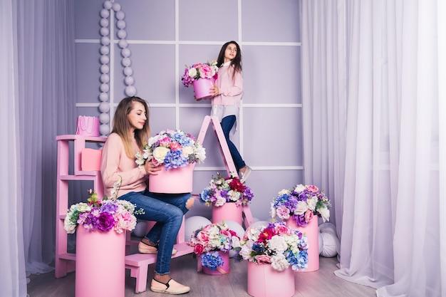 バスケットに花の装飾が施されたジーンズとピンクのセーターの2人の美しい女の子