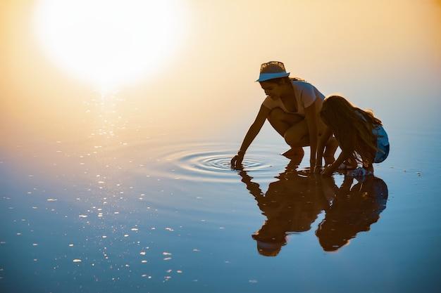 Две красивые девушки в нарядах на прозрачном соленом озере что-то ищут на блестящей поверхности