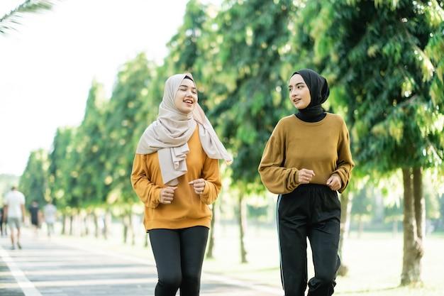 ベールに包まれた2人の美しい女の子が公園で一緒にジョギングしながらアウトドアスポーツをします