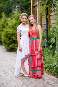 Две красивые девушки в белых и красных платьях.