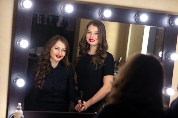 Две красивые девушки смотрят в зеркало